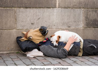 Man With a Horse Mask Laying on the Ground and the Dog is Sleeping on Man's Chest
