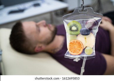 Man In In Hospital Getting IV Infusion Of Fruit Slices Inside Saline Bag