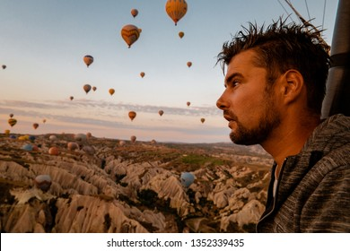man in hot air balloon watching Sunrise, hot air balloons during Sunrise over the fairytale landscape hills of Kapadokya, young men mid age in hot air balloon