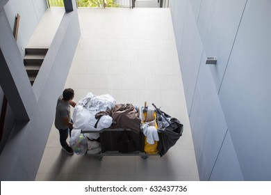 The man housekeeping pushing a cart for cleaning room in the hotel