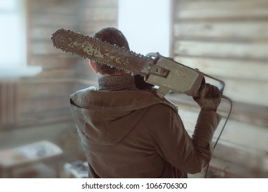 a man with a huge old chain saw on his shoulders in a wooden log hut