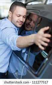 Man hugging a car in a car dealership