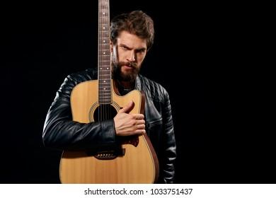 man hugging a guitar on a black background