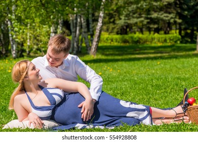 man hugging his beloved pregnant woman in the park