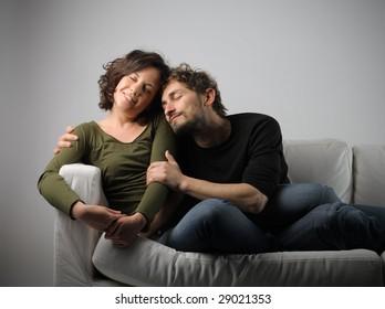 man hugging his girlfriend on a sofa