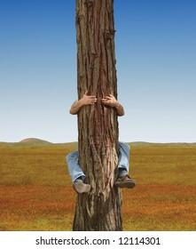 Man hugging a lone tree in a field