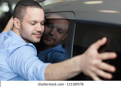 Man hugging on a car in a car dealership