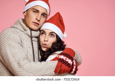 man hugging woman on a pink background, holiday, winter