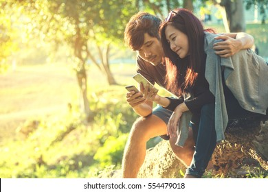 A man hugging a woman , sitting and using smartphones with feeling love in nature outdoor park