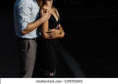 man hugs girl from behind on the street, hugging her, attracted to each other. girl in a black dress. man hugs from behind the woman and kisses on the forehead.the couple is standing against a dark