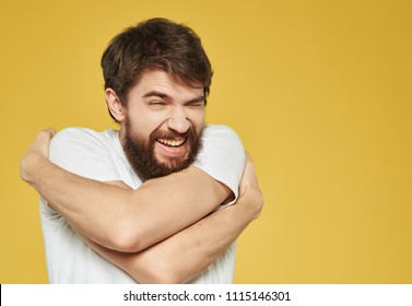 man hugs himself on a yellow background