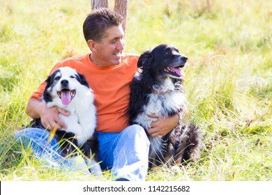 Man hugs his Australian Shepherd dogs while sitting in a field on a break from a walk on a sunny early fall day