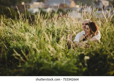 Man hugs tender woman in black dress sitting on the field