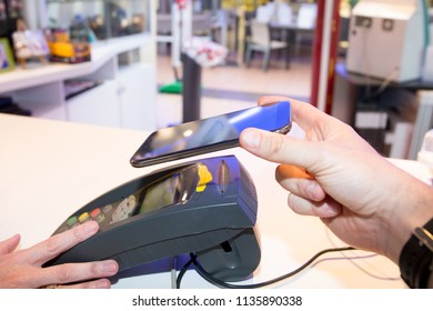 man Human hand with smartphone paying for order with help of swipe Contactless Mobile Phone to Credit Card System