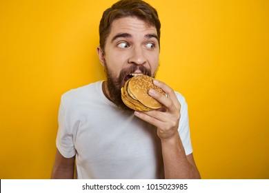 man hungry eats a hamburg on a yellow background