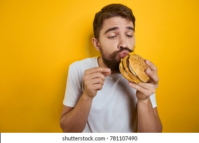 man hungry looks at a hamburger appetizing on a yellow background