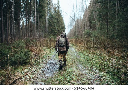 Man the hunter goes through the forest in rubber boots, with a backpack and a gun. Cloudy weather, autumn. On the ground, a little of snow. View from the back.