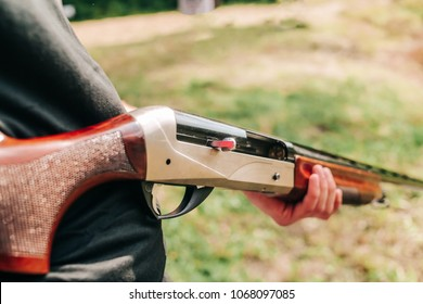 man hunter holds a shotgun with an open bolt and a cartridge inside the trunk