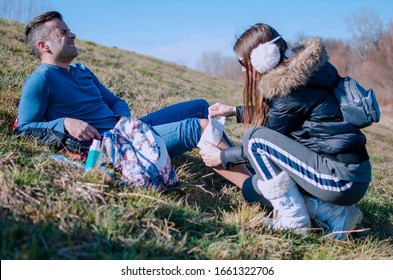 Man hurt leg muscle on climbing Knee Injury on hiking.Woman helping a man with first aid gauze to fixing the knee joint. Accident on mountain trail.Take Care of Pain in the male leg outdoors