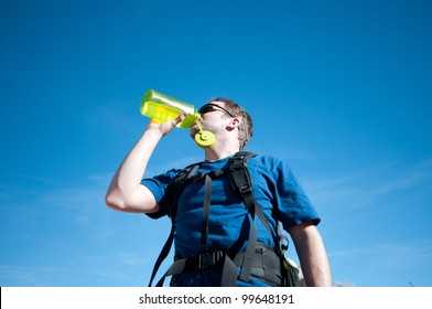 Man hydrates in desert, on hot, sunny day