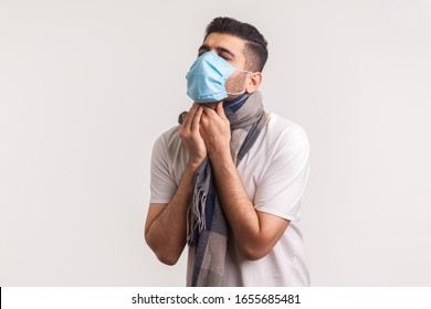 Man in hygienic mask and scarf suffering sore throat, coughing and suffocating, having symptoms of flu, contagious coronavirus infection 2019-nCoV. indoor studio shot isolated on white background
