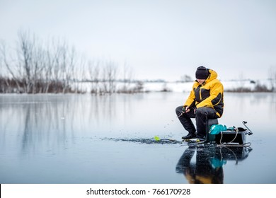 Man ice fishing on a frozen lake. winter holidays and people concept