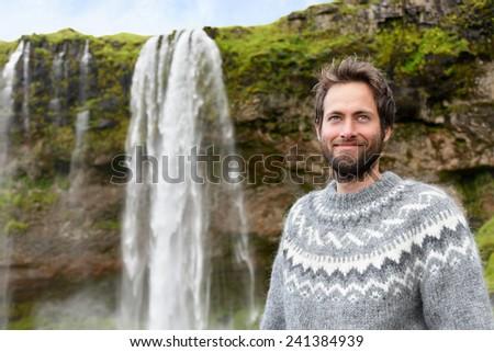 1867cefea27 Man in Icelandic sweater by waterfall on Iceland. Bearded male portrait of  good looking guy