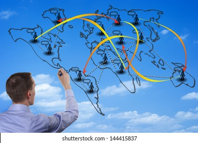 Man illustrating world population migration diagram on a glass wall, with his back to the camera.