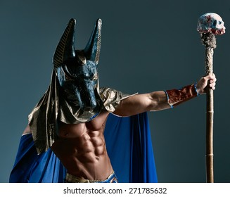 The man in the image of the ancient Egyptian Pharaoh  with a  mask of  Anubis on his face on blue background