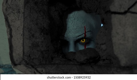 A man in the image of a clown peeps through a hole in the wall in old abandoned building.