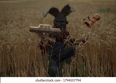 Man in image of sorcerer in hat with rabbit ears performs a voodoo ritual and holds doll impaled wire and old toy car on wheat field in evening.