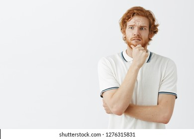 Man imaging his awful future if he get married frowning and feeling upset. Worried good-looking young redhead with beard holding hand on chin frowning and gazing left with nervous dissatisfied look