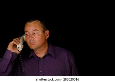 Man with an incredulous expression while holding a handset