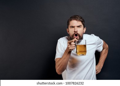 man indignant with beer on black background, alcohol