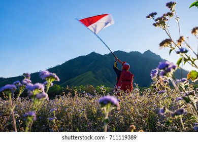 A man with Indonesian flag on Taman galuh, Bondowoso, East Java, Indonesia