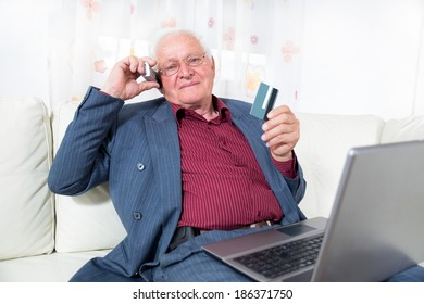 Man indoors using telephone and looking at credit card