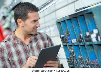 man in industrial warehouse holding clipboard