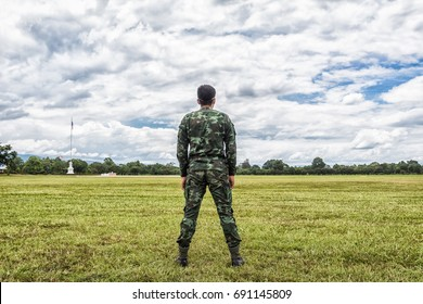 Man Infantry Army Soldier in Camouflage Uniform Standing on Grass with Beautiful Cloud Sky.