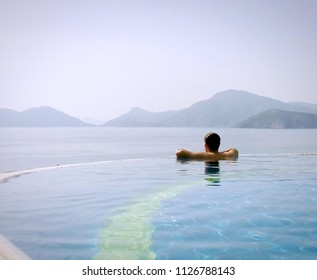 Man in infinity pool gazing at the serene view open to mountains and sea