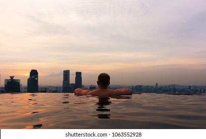 Man In Infinity Pool at Marina Skypark Bay in Singapore Skyline