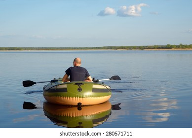 Man in an inflatable boat floats on the river, the view from the back.
