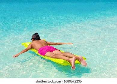 Man with inflatable color green mattress on summer vacations, enjoying life on tropical beach