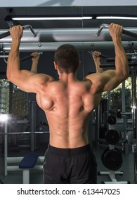 A man with an inflated back performs pull-ups on the crossbar
