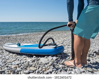 Man inflating stand up paddle board with manual pump at sea background