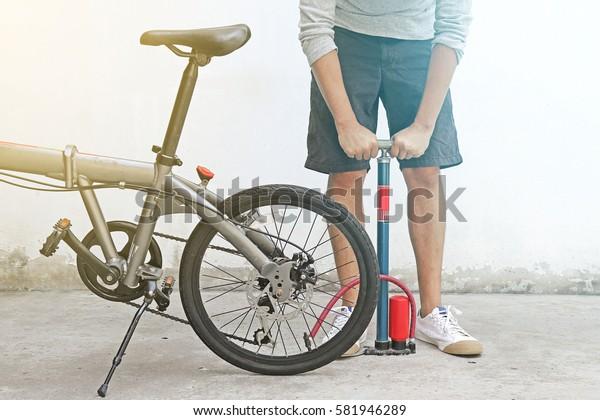 Man inflating tires of grey folding bike.