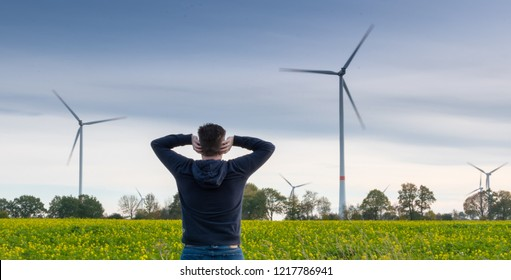 Man infront of a wind farm blocks his ears to reduce the noise