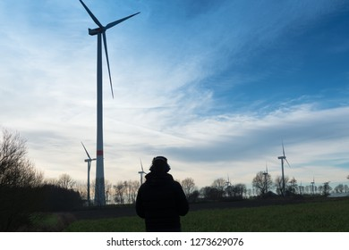 Man infront of a wind farm uses noise protector to reduce the noise of the wind turbine