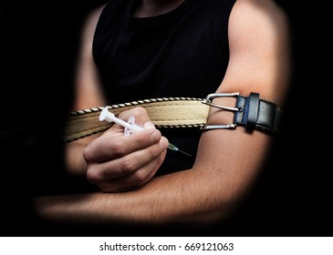 A man injects himself, tightening his arm with a belt, a black background