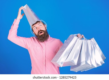 Man with insane look and open mouth wearing silver paper bag on his head. Shopaholic going crazy about seasonal sales, shopping concept. Bearded man in pink shirt isolated on blue background.