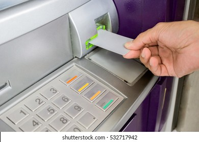 Man is inserting card to atm machine to withdraw or transfer money